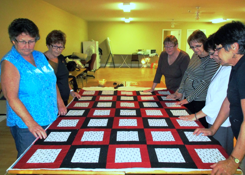 Tignish volunteers pinning a quilt
