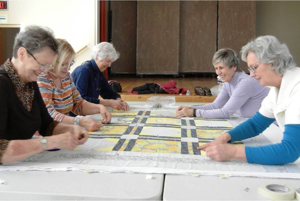 Volunteers pinning together a quilt
