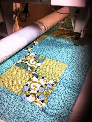 Fabric top being quilted using a long-arm sewing machine