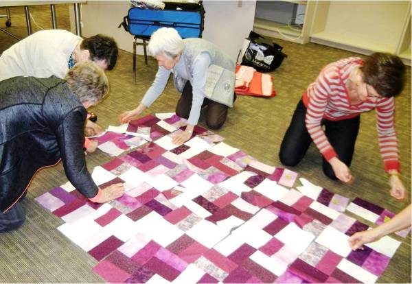 Volunteers laying out fabric pieces for a quilt top